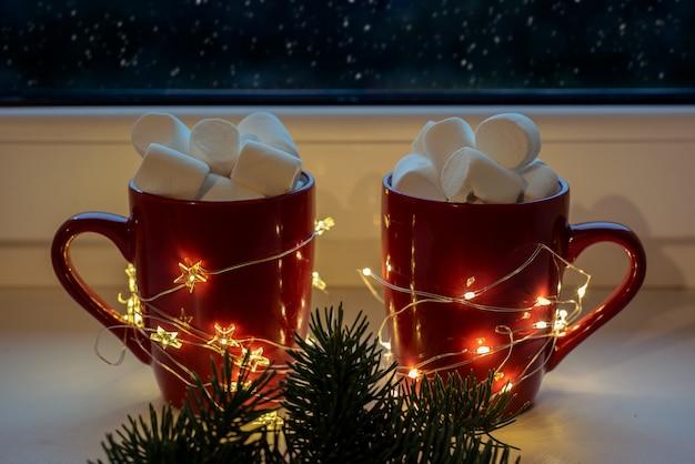 Czerwone kubki z gorącą czekoladą i ptasie mleczko z lampkami bożonarodzeniowymi i padającym śniegiem za oknem, wczasy świąteczne