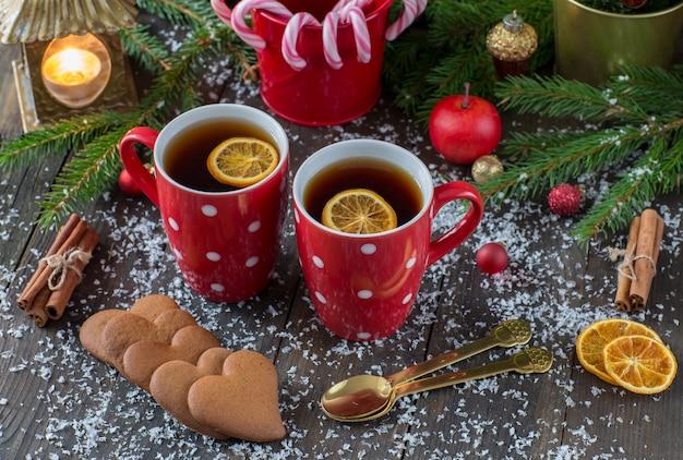Czerwone kubki z herbatą, trzciną karmelową, ciastkami w kształcie serca, jabłkiem, latarnią ze świecą