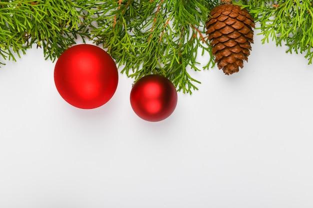 Czerwone kule na zielonych gałęziach, białe miejsca. pakowanie prezentów z czerwoną kokardką na białym polu. widok z góry. miejsce do pisania. przestrzeń bożego narodzenia.