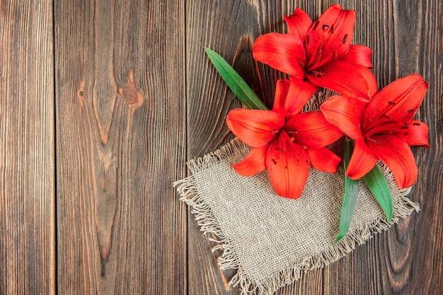 Czerwone lilie kwitną na ciemnym drewnie