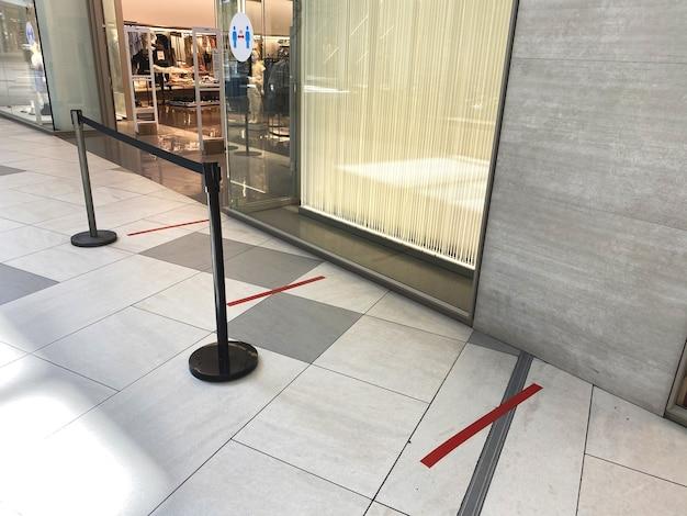 Czerwone linie dla osób stojących w kolejce w pobliżu sklepu