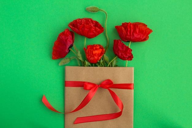 Czerwone maki w kopercie przewiązane czerwoną wstążką na zielono