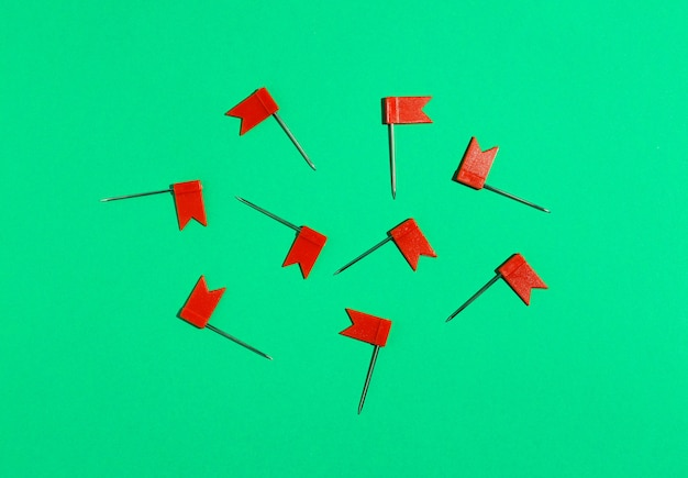 Czerwone małe szpilki flagi na zielonym tle. widok z góry .