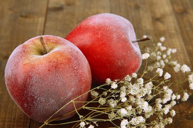Czerwone, matowe jabłka z kwiatami na drewnianej powierzchni
