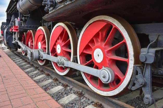 Czerwone metalowe koła, dwa koła lokomotywy parowej, żelazne koła