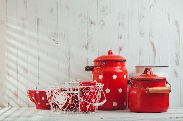 Czerwone naczynia kuchenne w kropki na białym stole