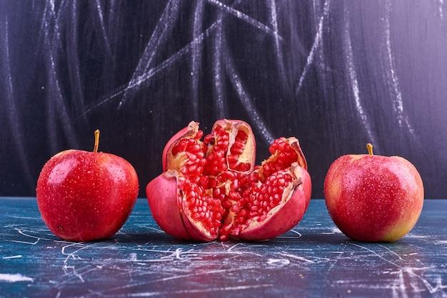 Czerwone nasiona granatu i jabłka na niebieskiej przestrzeni.