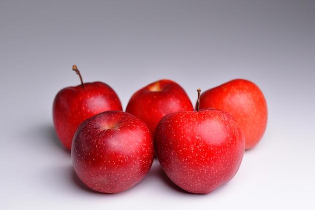 Czerwone naturalne jabłka jabłka bio zbierają surowe świeże owoce rolnicze na szarym tle