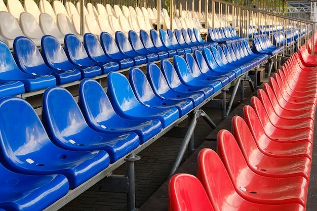 Czerwone, niebieskie i białe fotele stadionów sportowych. puste stojaki.