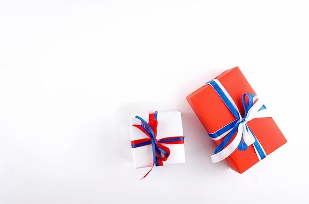 Czerwone, niebieskie i białe pudełka na prezenty na białym tle, koncepcja święta niepodległości, urodziny, impreza