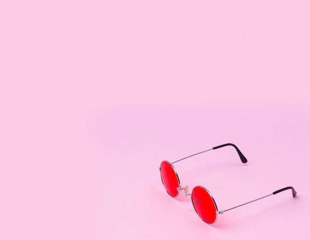 Czerwone okulary na pastelowych różach z miejsca na kopię.