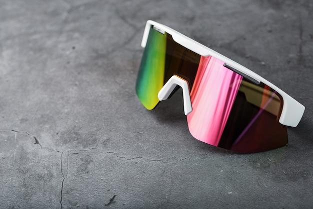 Czerwone okulary sportowe z lustrzanymi soczewkami na ciemnej powierzchni
