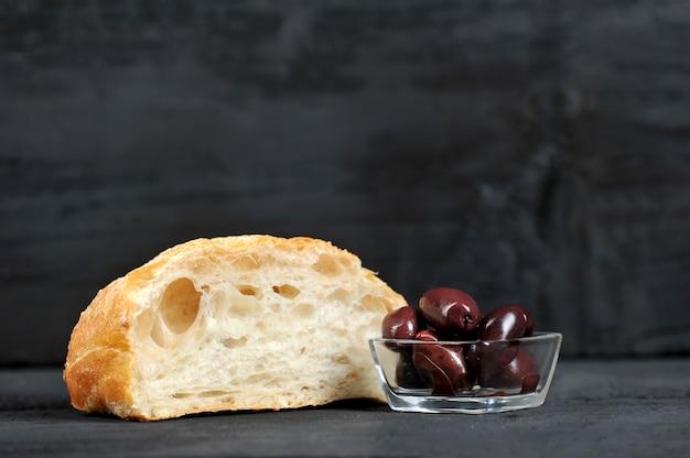 Czerwone oliwki w szklanym talerzu i ciabatta
