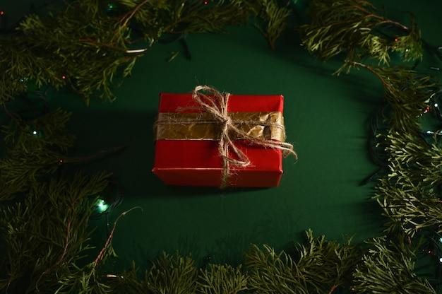 Czerwone opakowanie na prezent na ciemnym tle z wiecznie zielonymi gałęziami i światłami
