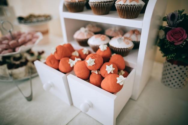 Czerwone pączki i ciasta w białych drewnianych pudełkach na stole deserowym. batonika