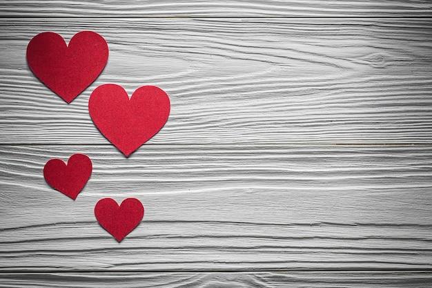 Czerwone papierowe serca na desce