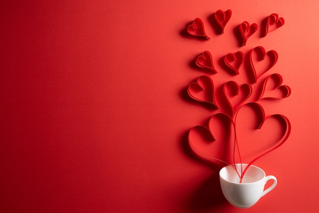 Czerwone papierowe serca tryskają z filiżanki kawy