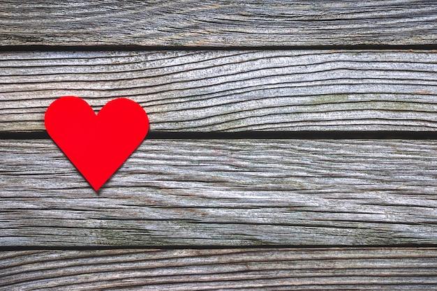 Czerwone papierowe serce na drewnianym tle