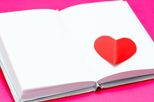Czerwone papierowe serce nad białą otwartą książką na różowej powierzchni
