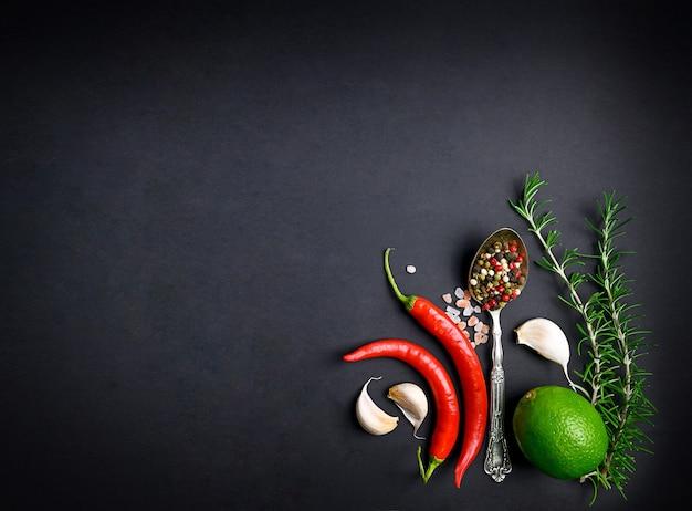 Czerwone papryczki chili, czosnek, liść laurowy, rozmaryn i różne przyprawy na czarnym tle