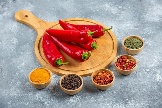 Czerwone papryczki chili na desce z przyprawami.
