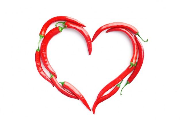 Czerwone papryczki chili ułożone w formie serca na białym tle. koncepcja pasji, uzależnienia od pikantnych potraw, walentynki