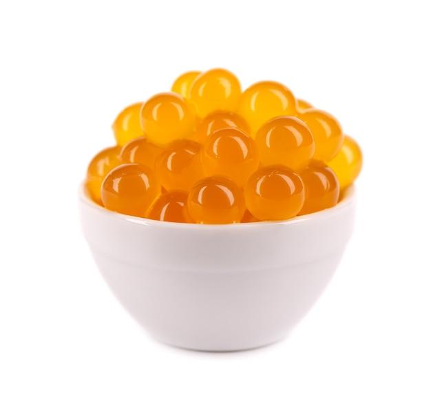 Czerwone perły tapioki na herbatę bąbelkową na białym tle. perły tapioki w białej ceramicznej łyżeczce.