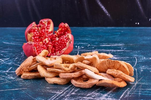 Czerwone pestki granatu i suche plasterki jabłka.
