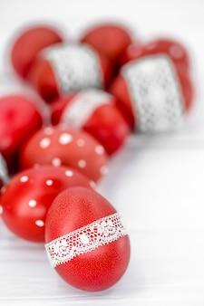 Czerwone pisanki na białej taśmie koronki wiązanej, zbliżenie, leżące na białym drewnie