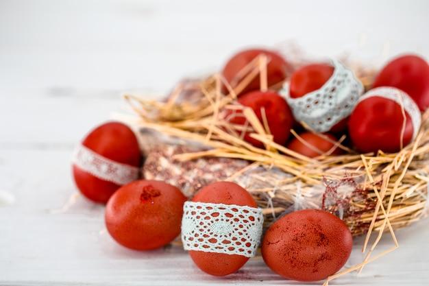 Czerwone pisanki w gnieździe siana