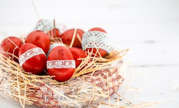 Czerwone pisanki w gnieździe z siana, przewiązane koronkową wstążką, zbliżenie, leżące na białym drewnie