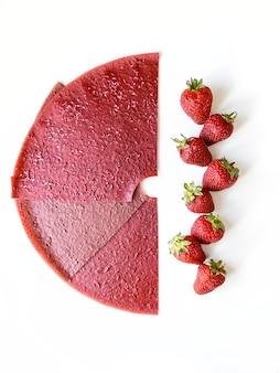 Czerwone plasterki skóry owoców truskawek i jagody na białym tle. widok z góry, płaski układ.