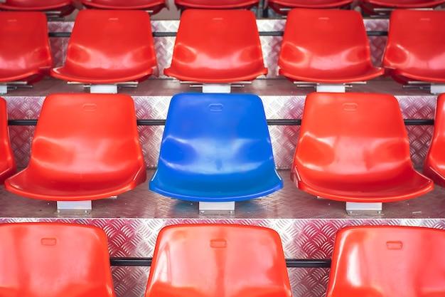 Czerwone plastikowe krzesła z niebieskimi siedzeniami w środku. zauważ odwagę, by być innym.