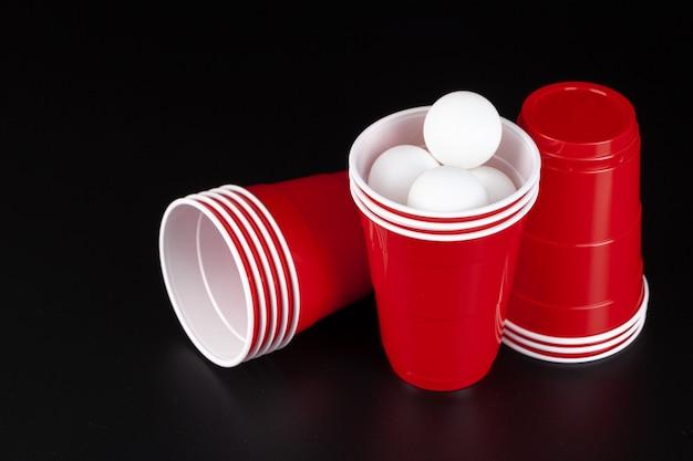 Czerwone plastikowe kubki i piłka do gry w piwnego ponga