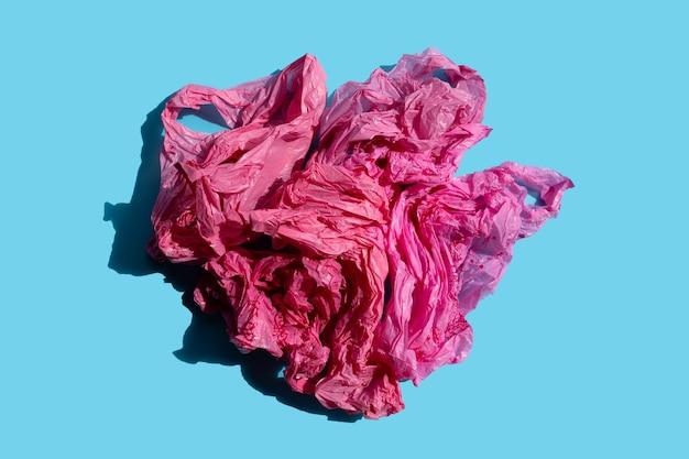 Czerwone plastikowe torby na niebieskiej powierzchni