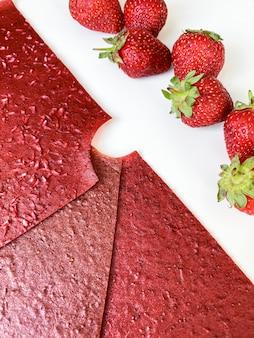 Czerwone plastry skóry owoców truskawek i jagody na białym tle. widok z góry, płaski układ