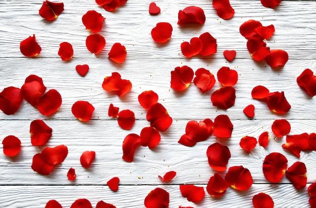 Czerwone płatki róż i małe czerwone drewniane serca na białym tle drewnianych. widok z góry. tło walentynki.
