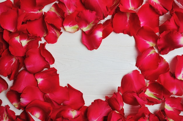 Czerwone płatki róż w kształcie serca na tle walentynki