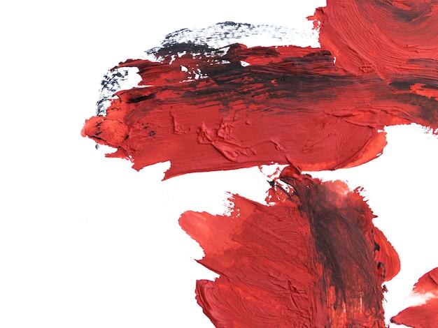 Czerwone pociągnięcia pędzlem z czarnymi śladami