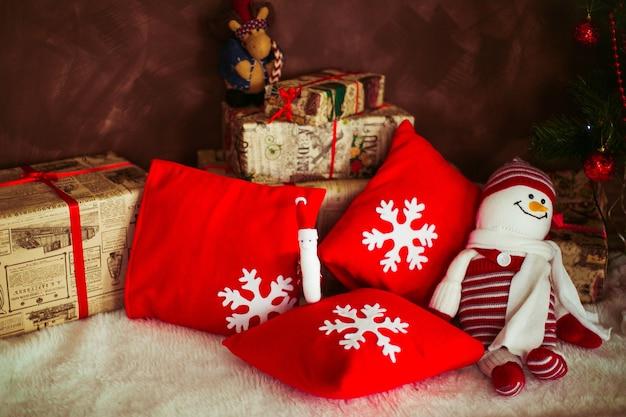 Czerwone poduszki z śnieżynkami i bałwanek z zabawkami leżą na podłodze