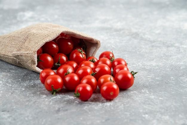 Czerwone pomidorki koktajlowe z rustykalnego kosza na marmurowym stole.