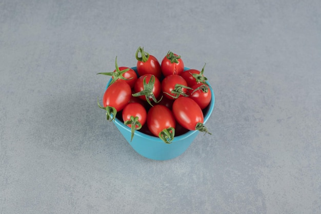 Czerwone pomidory czereśniowe na białym tle na betonowym stole.