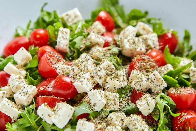 Czerwone pomidory czereśniowe z serem sałatkowym, rukolą i przyprawami. danie sałatka jarzynowa, zbliżenie