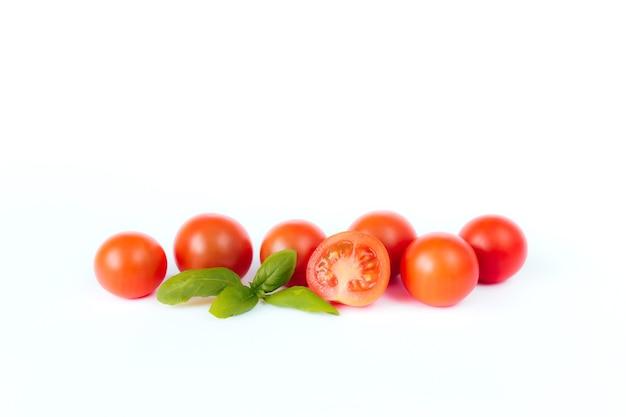 Czerwone pomidory czereśniowe z zieloną bazylią na białym tle. wysokiej jakości zdjęcie