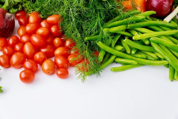 Czerwone pomidory czereśniowe, zielony groszek i koper na białym stole.