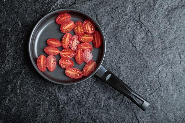 Czerwone pomidory koktajlowe pokrojone na pół na patelnię.