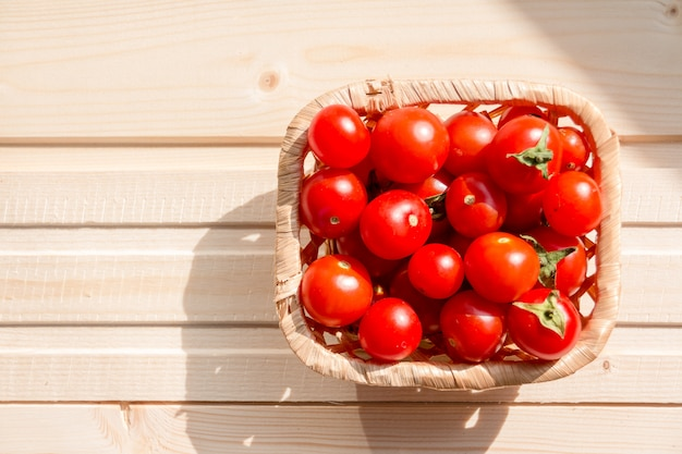 Czerwone pomidory koktajlowe w koszu na drewnianym stole. zdrowe, świeże pomidory koktajlowe bez organizmów modyfikowanych genetycznie. organiczne pomidory winogronowe