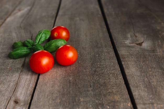 Czerwone pomidory koktajlowe z zieloną bazylią na szarym tle drewnianych