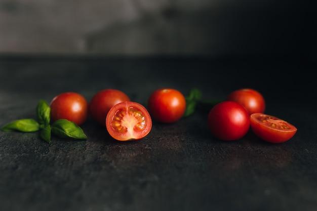 Czerwone pomidory koktajlowe z zieloną bazylią na szarym tle