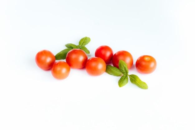 Czerwone pomidory koktajlowe z zieloną bazylią.